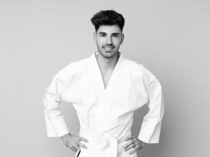 Mann im Karate-Anzug mit den Armen auf die Hüfte gestützt - fröhlich